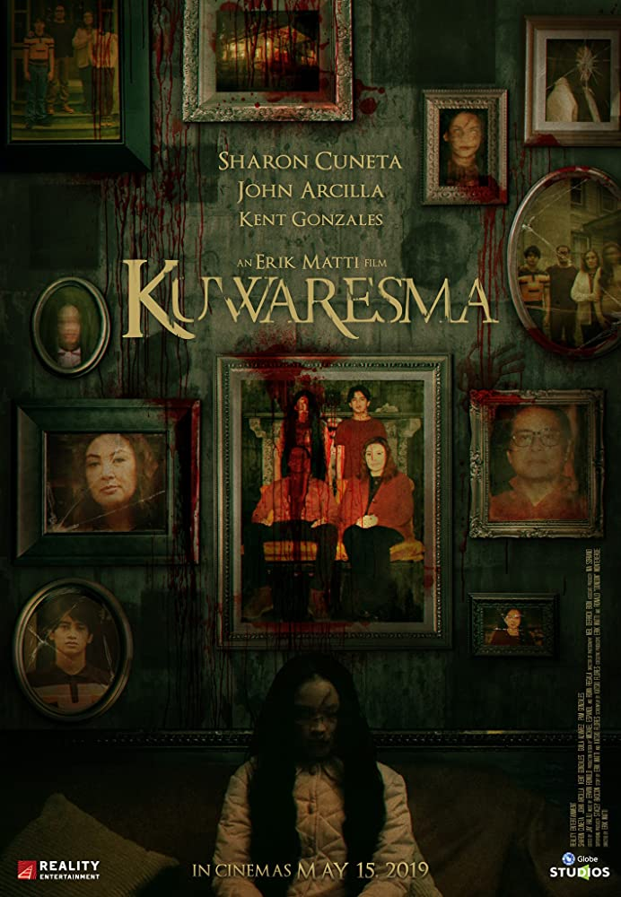 The film poster showing a wall full of family portraits, splattered in blood, a ghost girl sitting in front of it.