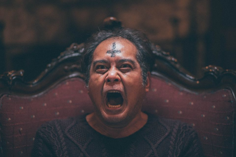 Arturo (John Arcilla) with a cross painted upside down on his forehead. He is screaming.