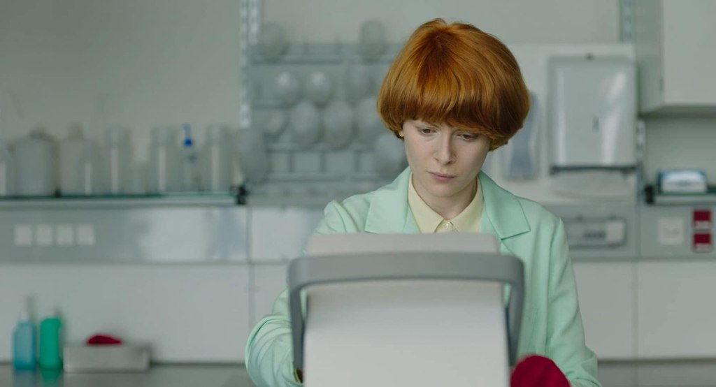 Alice (Emily Beecham) working at a lab instrument.