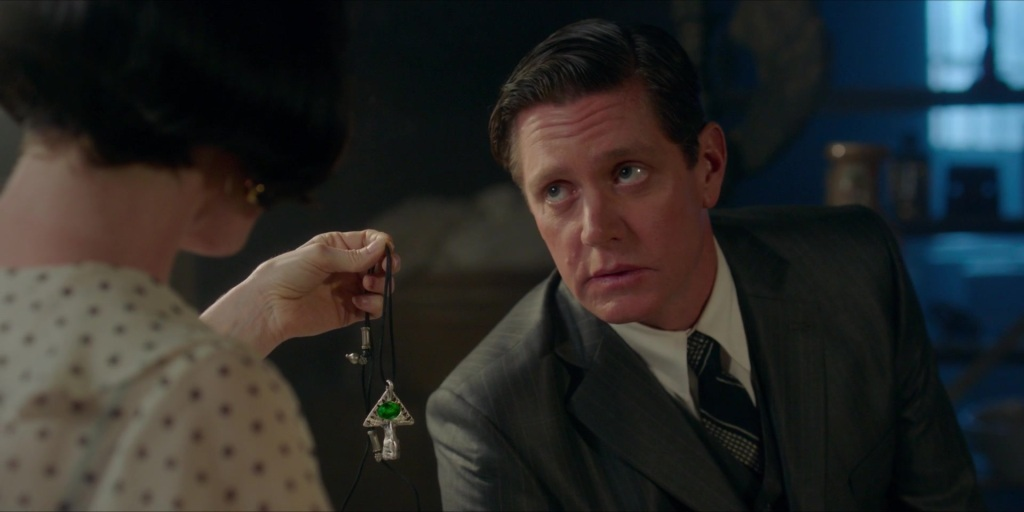 Phryne Fisher (Essie Davis) holds up a necklace to Jack Robinson (Nathan Page).