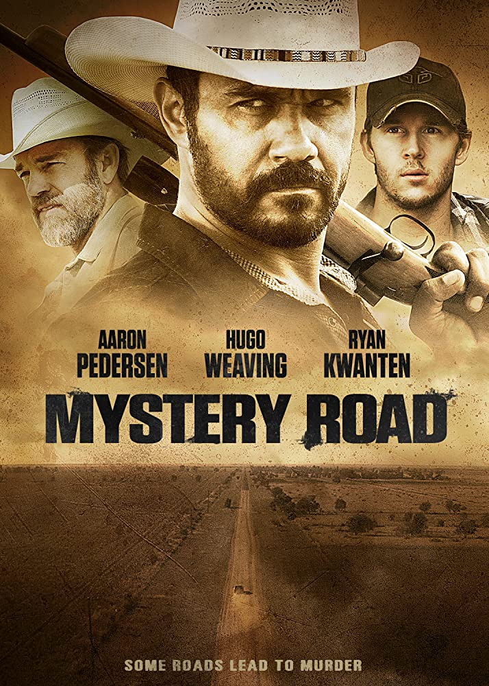 The film poster showing a lone car on a dirt road and the heads of three of the main characters.