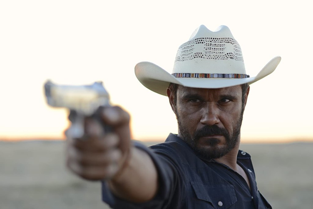 Detective Jay Swan (Aaron Pedersen) aiming his gun.