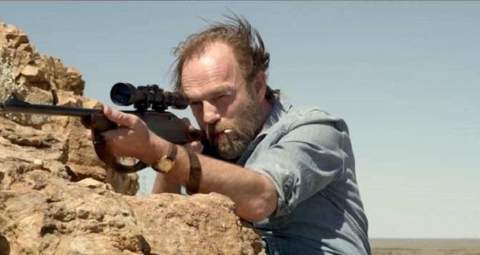 Johno (Hugo Weaving) aiming his gun.