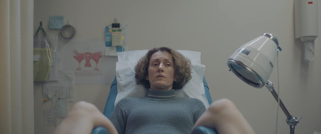 Elpida (Stella Fyorgeni) at a gynecological exam.