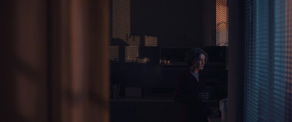 Elpida (Stella Fyorgeni) looking out the window in the dark.