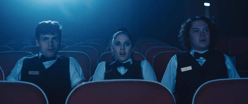 Abe (Evan Daves), Chaz (Jillian Mueller), and Ricky (Glenn Stott) watching a film together, looking shocked.