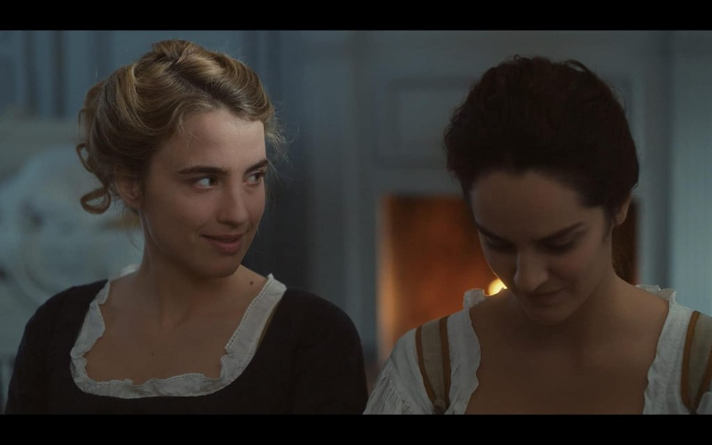 Héloïse (Adèle Haenel) smiling at Marianne (Noémie Merlant) who is looking down.