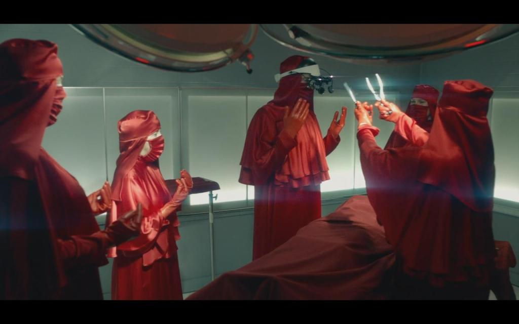 An operating room with the staff all wearing blood-red scrubs and veils.