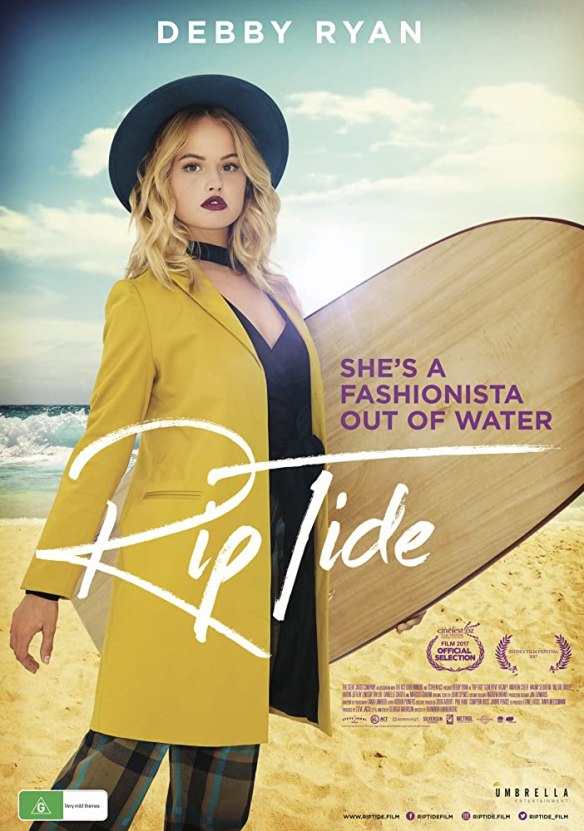 The film poster showing Cora (Debby Ryan) in fashionable clothes with a surfboard in her hand.