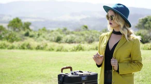 Cora (Debby Ryan) standing in a fashionable outfit with a suitcase in the middle of nowhere.