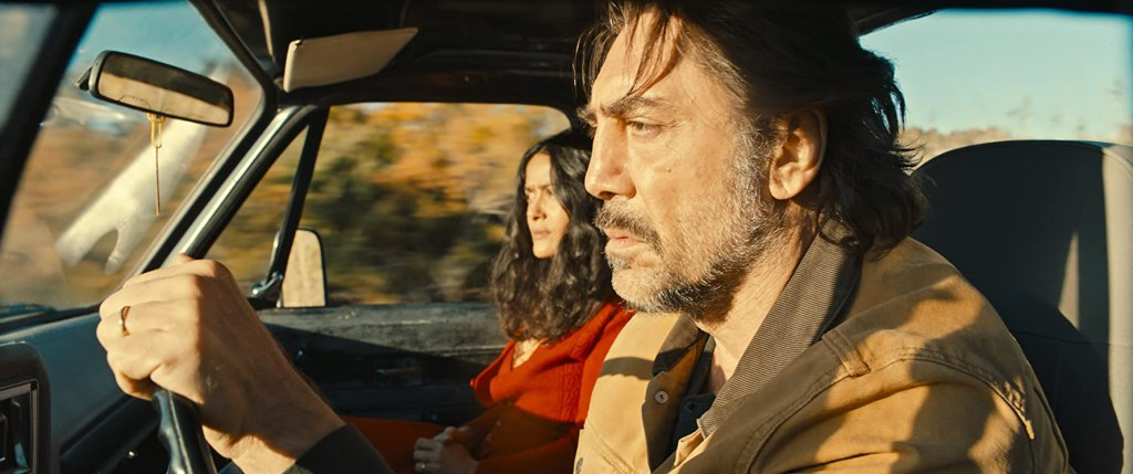 Leo (Javier Bardem) driving in the car with Dolores (Salma Hayek).