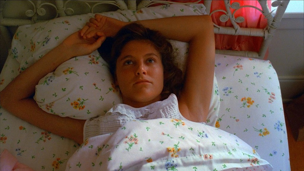 Trish (Michelle Michaels) lying in bed.