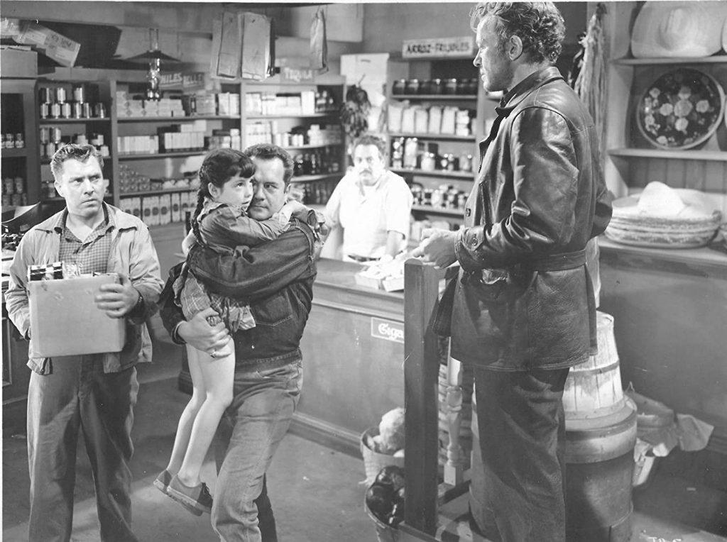 Gilbert (Frank Lovejoy) holding a litttle girl in a grocery story while Emmett (William Talman) talks.