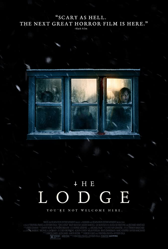 The film poster showing a window from a cabin in the snow, three blurry humans can be seen inside.