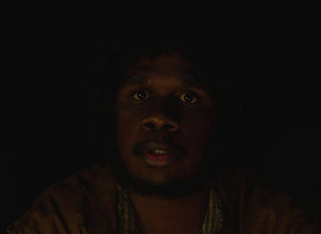 Billy (Baykali Ganambarr) sitting in the dark.
