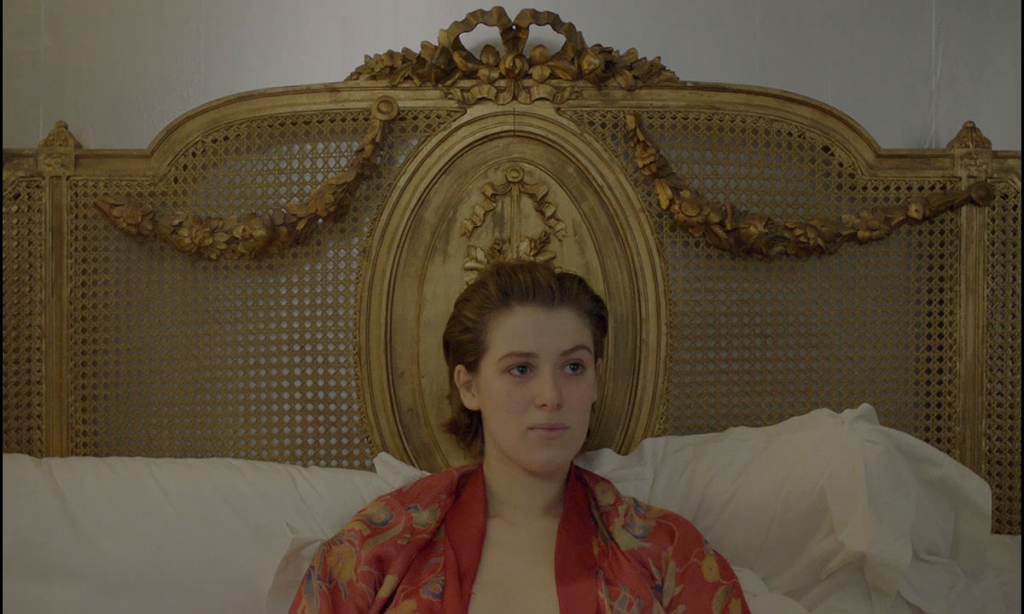Julie (Honor Swinton Byrne) sitting in an ornate bed.