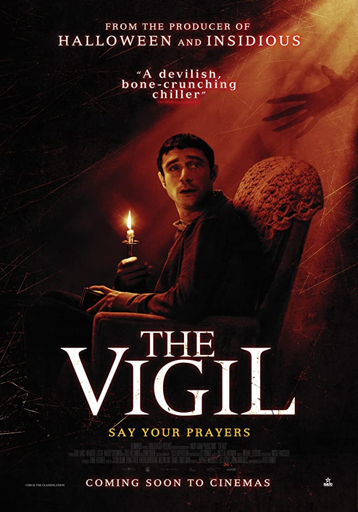 The film poster showing Yakov (Dave Davis) sitting in an arm chair with a brungin candle. A shadowy hand is reaching for him.