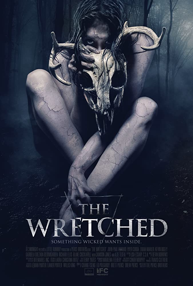 The film poster showing a woman with flaking skin hiding behind a deer skull.