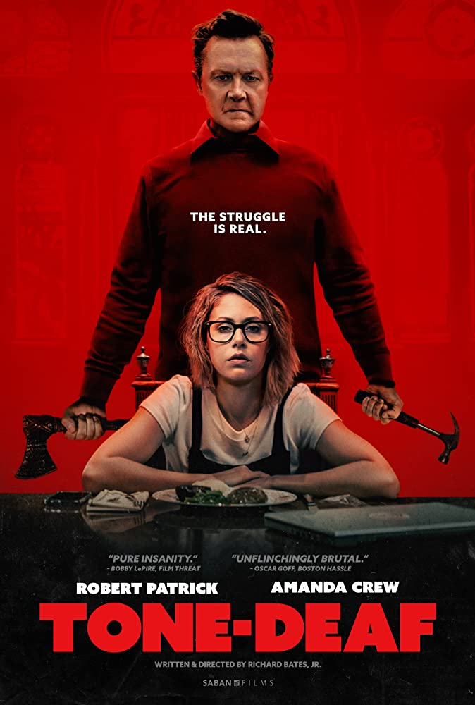 The film poster showing Olive (Amanda Crew) sitting at a table with Harvey (Robert Patrick) standing behind her, an axe in one hand a hammer in the other.