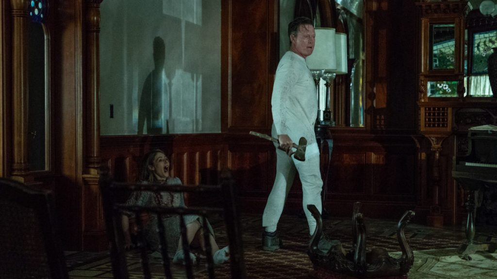 Olive (Amanda Crew) screaming in a bloodied whtie dress while Harvey (Robert Patrick) stands over her with an axe.