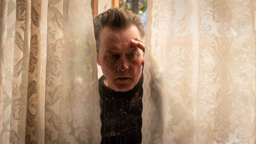 Harvey (Robert Patrick) looking in through the window.