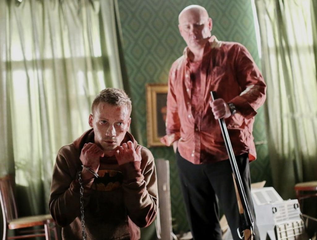 Matvey (Aleksandr Kuznetsov) kneeling with his hands tied, Andrey (Vitaliy Khaev) at his back with a shotgun.