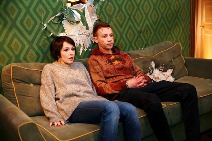 Olya (Evgeniya Kregzhde) and Matvey (Aleksandr Kuznetsov) sitting on the couch.