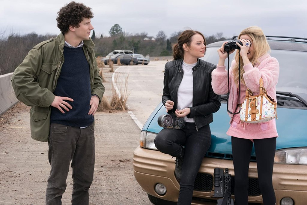 Columbus (Jesse Eisenberg) and Wichita (Emma Stone) look at Madison (Zoey Deutch) who is looking through binoculars the wrong way round.