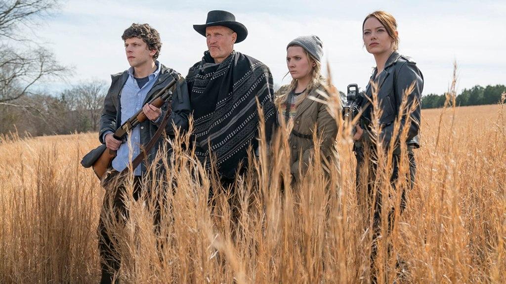 Little Rock (Abigail Breslin), Tallahassee (Woody Harrelson), Wichita (Emma Stone) and Columbus (Jesse Eisenberg) walking through a field, weapons ready.
