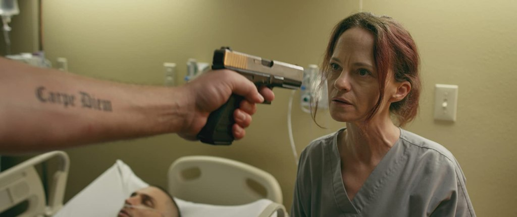 Mandy (Angela Bettis) with a gun pointed at her face.