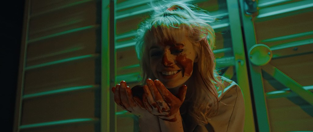 Regina (Chloe Farnworth) with blood all over her face and hands, cradling an organ and smiling at it.