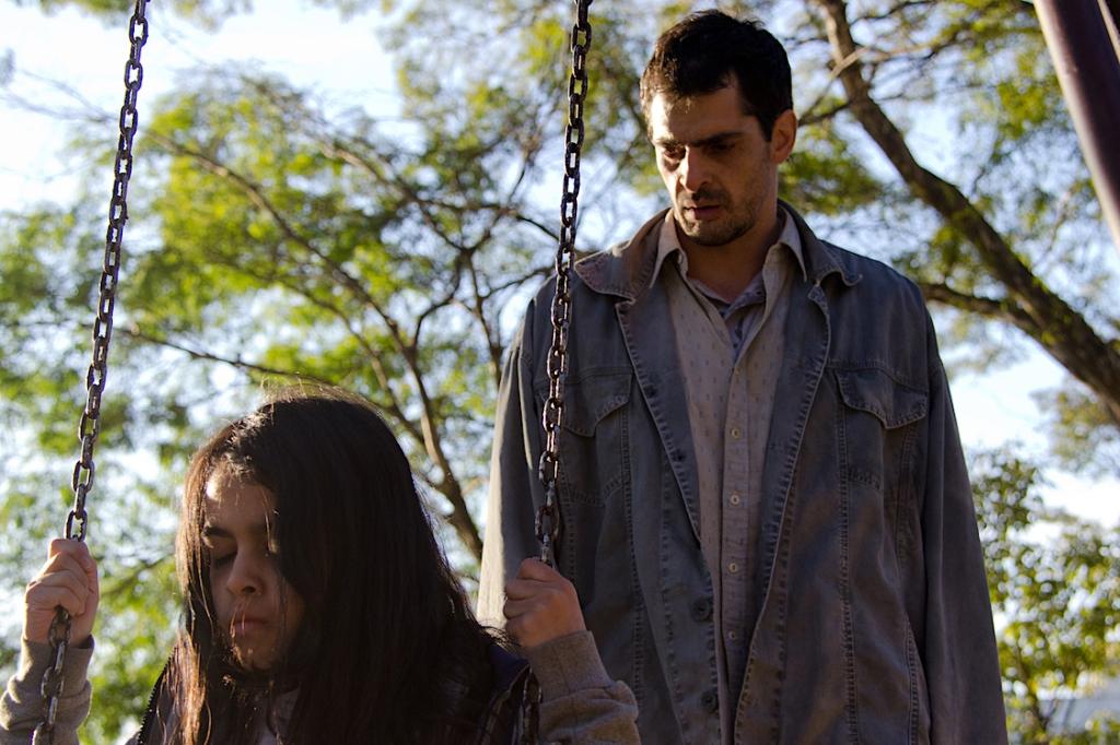 Dalva (Nina Medeiros) and Jorge (Julian Machado) at the swings.