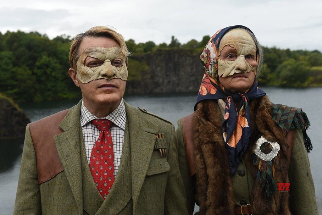 The Duke (Eddie Izzard) and the Duchess (Georgie Glen) in strange masks.
