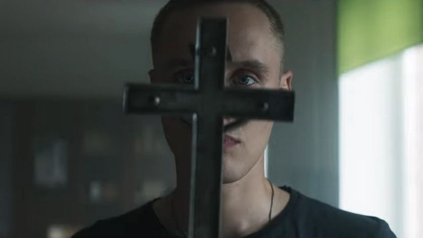 Daniel (Bartosz Bielenia) holding a cross so his face is covered.