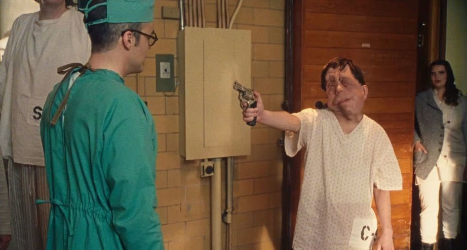 Rosenthal (Adam Pearson) wearing a hospital gown and pointing a gun at a doctor.