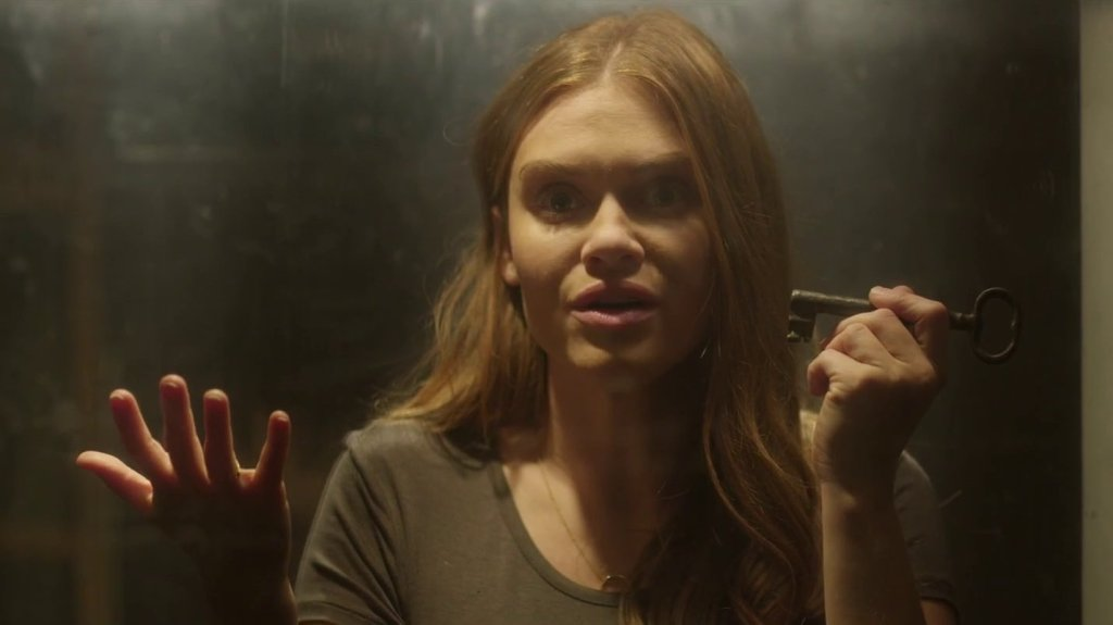 Erin (Holland Roden) inside a glass tank with a puzzled expression and a key in her hand.
