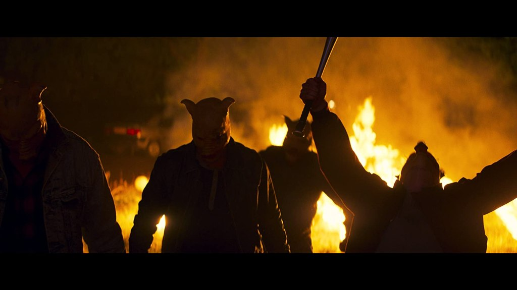 A group of men in pig masks walking away from a fire.