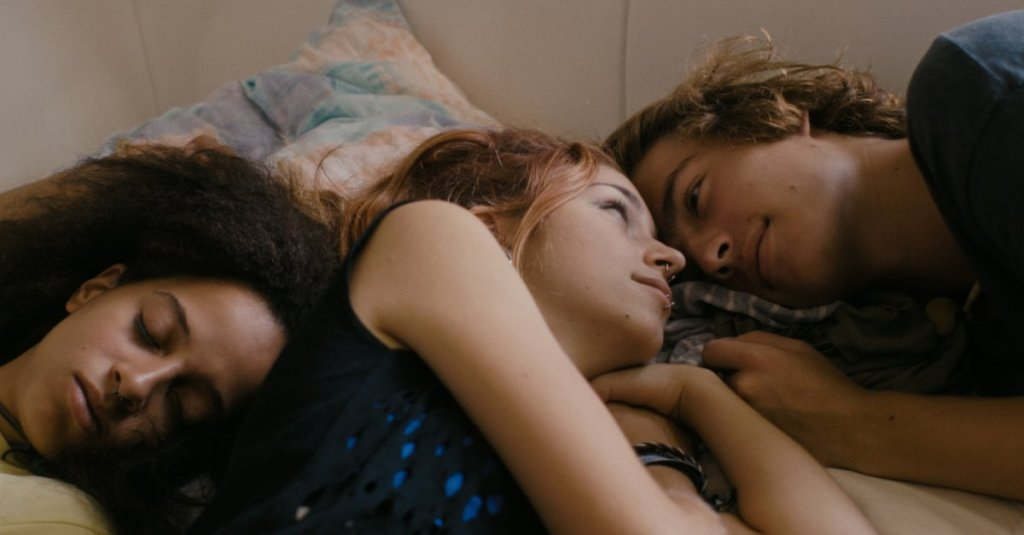 Luka (Lou von Schrader) and Ben (Max Kuess) looking at each other while lying next to sleeping Momo (Melissa Irowa).
