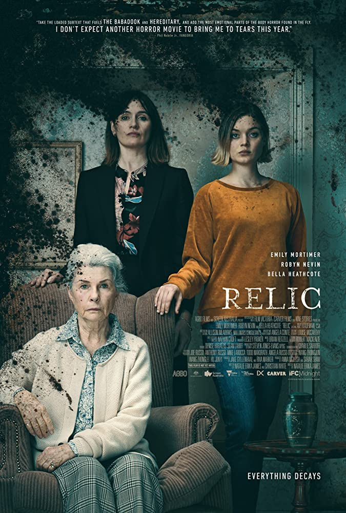 The film poster showing Edna (Robyn Nevin), Kay (Emily Mortimer) and Sam (Bella Heathcote) standing like a family portrait. Black mold is in the corner of the picture.