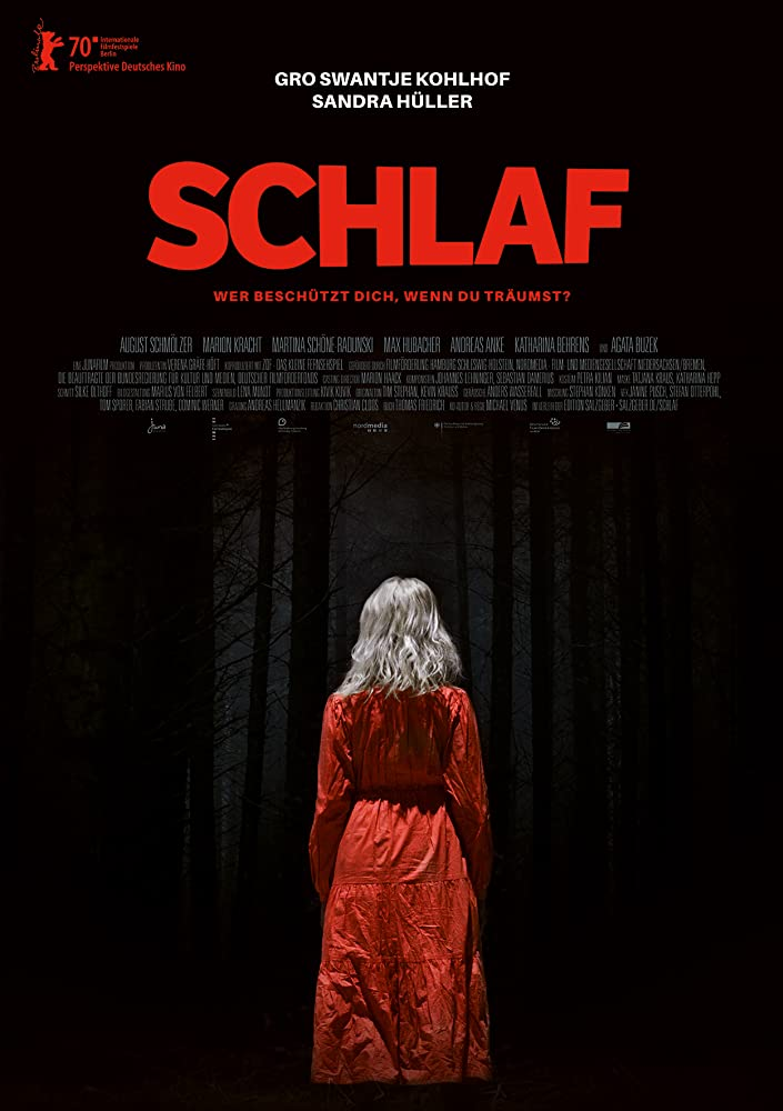 The film poster showing a blond woman in a red dress with her back to the camera in a forest so dark, it's almost entirely black.