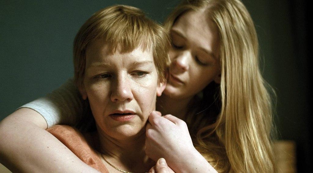 Mona (Gro Swantje Kohlhof) hugging Marlene (Sandra Hüller) from behind.