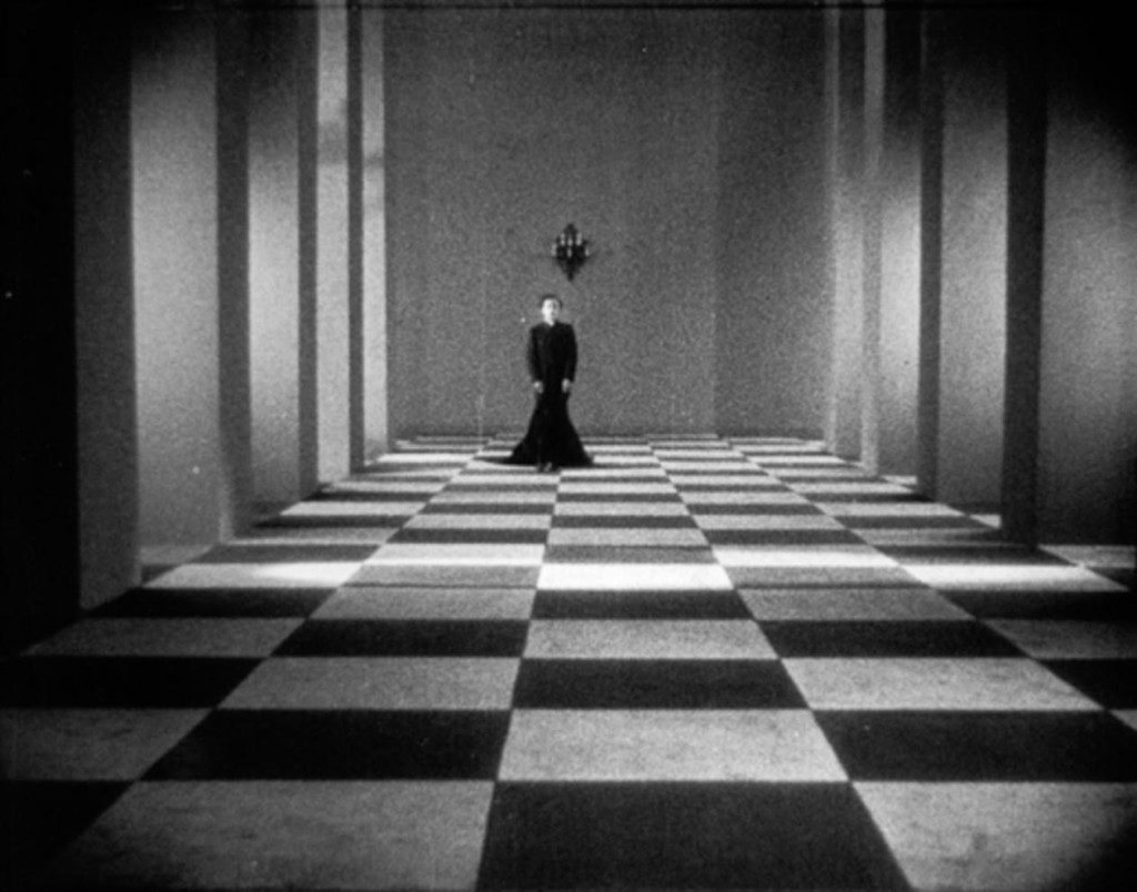 The clergyman (Alex Allin) walking through a hallway with checkered tiles.