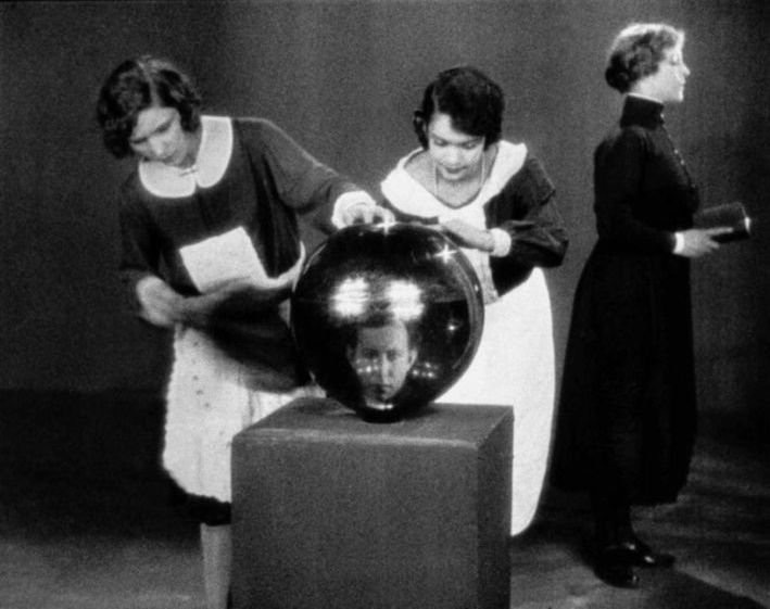 Two maids polishing a giant reflective orb.