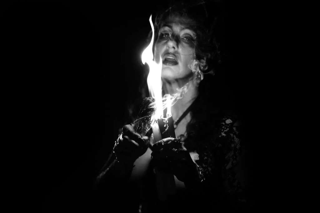 Black and white image: The High Priestess (Sadie Lune) lighting a candle.