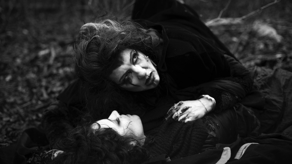 Black and white image: The High Priestess (Sadie Lune) cowering over the midwife (Dion De Rossi).