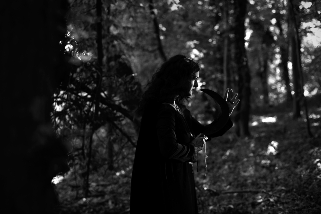 Black and white image: The High Priestess (Sadie Lune) walking thorugh the woods.