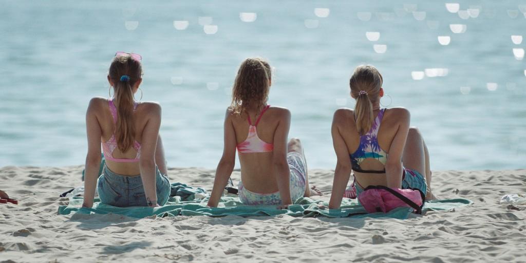 Three girls - Claire (Zita Gaier), Chantal (Flora Thiemann) and Sandra (Anima Schwinn) - sitting on the beach looking out at the sea.