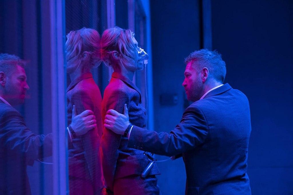 Andrei (Kenneth Branagh) pressing Kat (Elizabeth Debicki) against a glass wall. She is wearing a breathing mask.