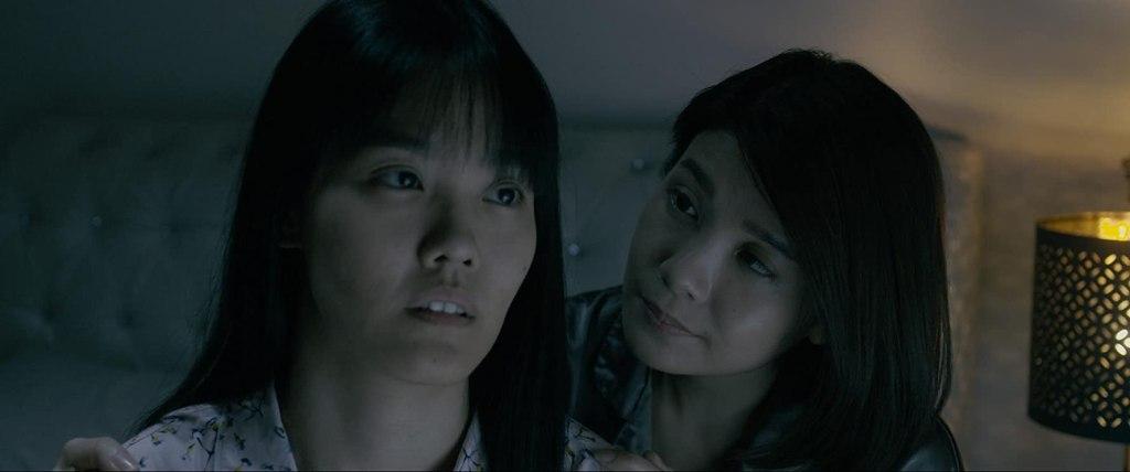 Mei Xi (Emily Lim) comforting Mei Yue (Lim Mei Fen) who looks dazed.