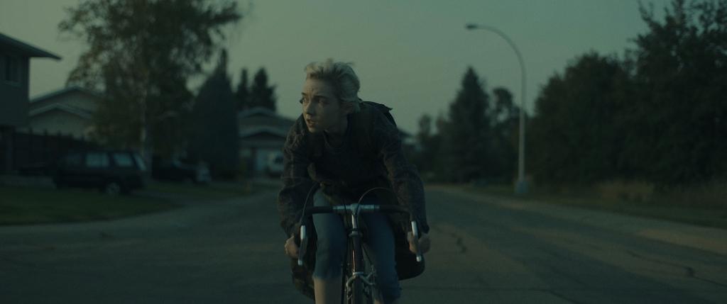 Sarah (Julia Sarah Stone) on her bike, cycling through the city.